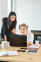 Two young businesswomen using laptop computer in work while working at the workplace at office