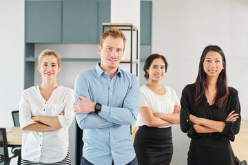 Portrait of successful male leader standing with arms crossed together with his young business team of women