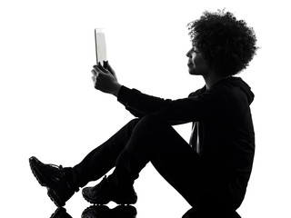 one mixed race african young teenager girl woman using digital tablet in studio shadow silhouette...