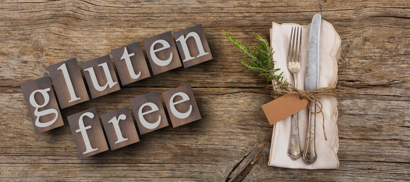 Gluten-free text and cutlery on rustic wooden table, top view. 3d illustration