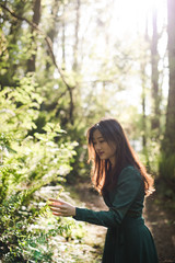 Young woman touching leaves in forest