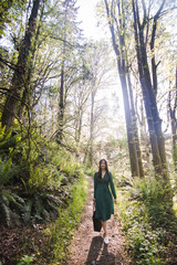 Portrait of young woman with bag walking on forest road