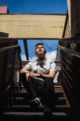 Thoughtful young man sitting on staircase outdoors