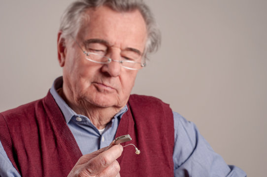 Worried senior man holding hearing aid