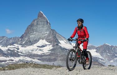 active senior woman, riding her electric mountainbike below the famous Matterhorn in Zermatt, Wallis,Switzerland
