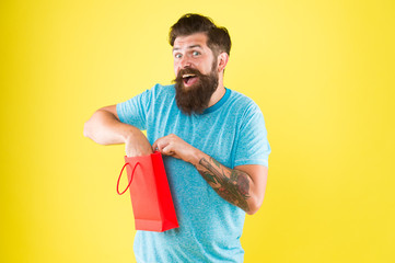 Happy hipster hold paper bag. Bearded man smiling with purchase. Impulse purchase. Shopping concept. Shop store mall boutique. Buy product. Aspects can influence customer decision making behavior