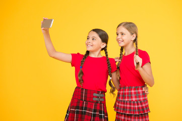 lets make pic. girls in uniform. small girls making selfie on phone. having fun. sisterhood and friendship. happy knowledge day. childhood happiness. education concept. back to school. social network