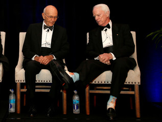 Apollo 11 astronaut Michael Collins (L) looks at socks picturing Saturn V rocket worn by Apollo 9 astronaut Rusty Schweikart as they take part in a panel discussion on the 50th anniversary of Apollo 11 launch, in Cocoa Beach