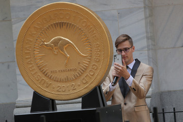 A man takes a photo of the world's largest gold bullion coin, the Australian Kangaroo One Tonne Gold Coin, is displayed outside the NYSE in New York