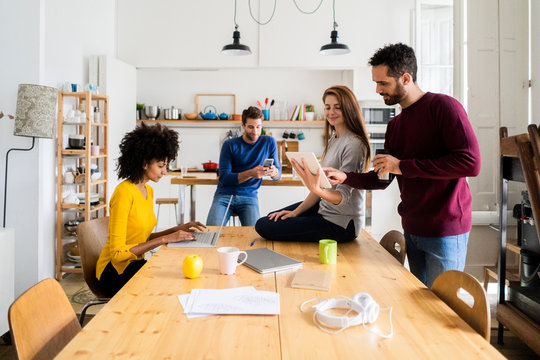 Four friends in dining room at home with portable devices