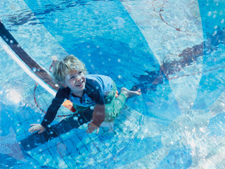 Portrait of little boy having fun with bech ball and swimming pool