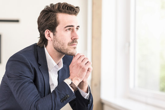 Pensive businessman sitting at the window