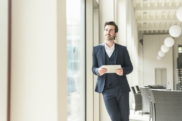 Young businessman standing in office building, using digital tablet Wall mural