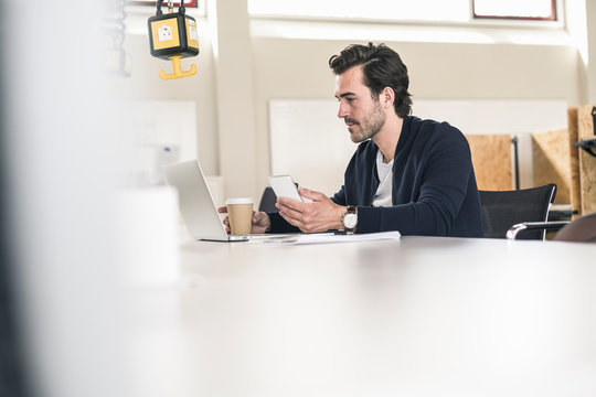 Young businessman sitting in office, using laptop and smartphone