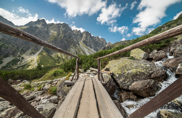 Cloudy Mountain Landscape with Wood Bridge for Hiking and Water Cascades during the Day in High Tatras, Slovakia