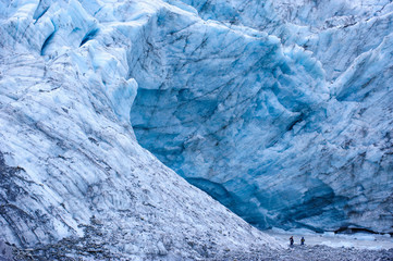 Tourists hiking to the giant glacial outflow of Fox Glacier, South Island, New Zealand