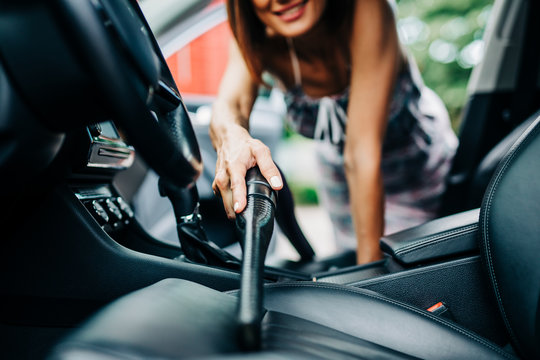 Interior car detailing. Happy middle age woman cleans the interior of her car with vacuum cleaner.