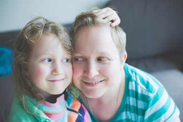 Portrait of smiling mother with daughter at home