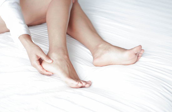 Close up woman touching her heel with pain lying on white bed, health care concept