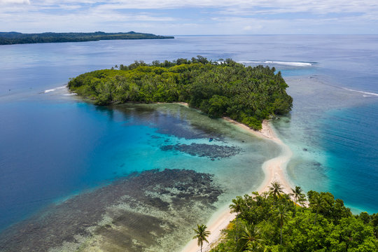 A coral reef surrounds idyllic islands off the coast of New Britain in Papua New Guinea. This area is part of the Coral Triangle due to its high marine biodiversity.