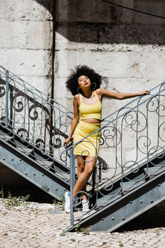 Beautiful African American woman in yellow suit standing and leaning in railing and looking away on urban background