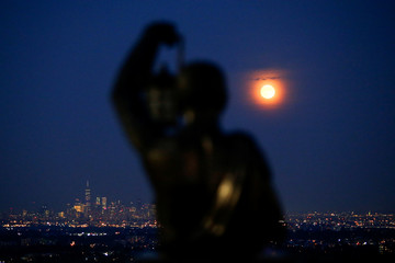 The full moon known rises over the skyline of New York and One World Trade Center as seen from West Orange in New Jersey