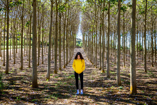 Beautiful young female with long black hair standing in yellow sweatshirt on nature background and looking down