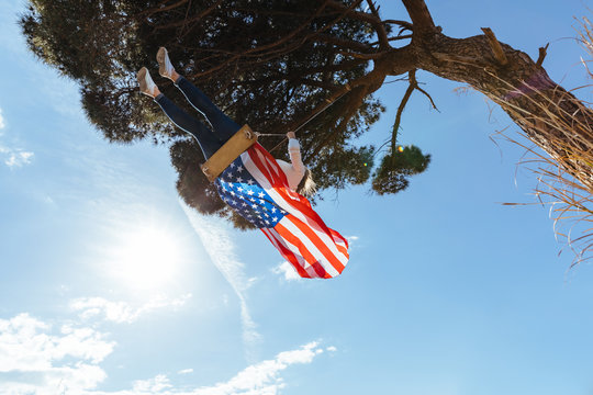 Young girl celebrating the 4th of July with the American flag on a swing