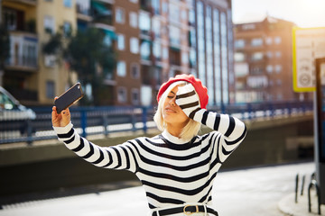 Young smiling pretty woman in French red cap, striped blouse and white shorts taking photo on urban background