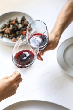 From above crop hands of people clinking with wine glasses while eating delicious meal on white background