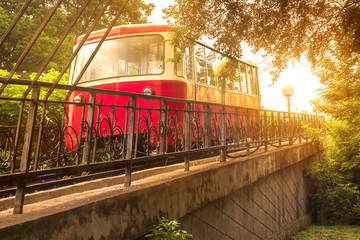 The Red Car of the Funicular rises in the bright sunlight of an evening sunset in the capital of the Russian Far East, Vladivostok