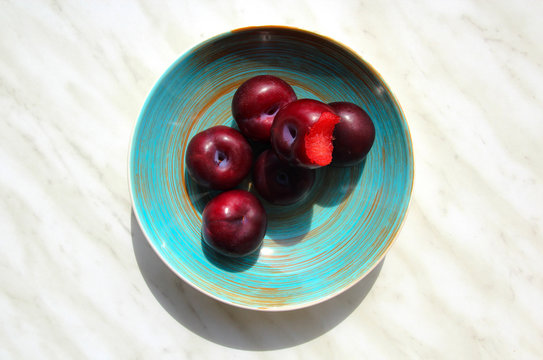 From above appetizing ripe bitten plum and whole fruit in round blue plate on marble background