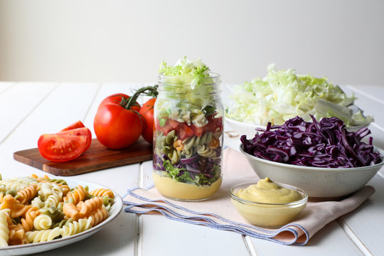 Yummy pasta with fresh vegetables and sauce placed inside jar on white table