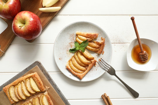 From above piece tasty apple pie with honey and mint leaves with cinnamon placed on plate over white table