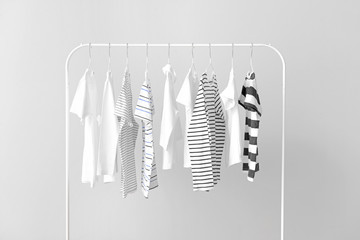 Stylish kid clothes hanging on rack against light background