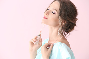 Fototapeta Beautiful young woman with bottle of perfume on color background