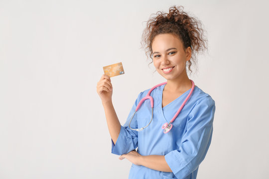 African-American doctor with credit card on light background