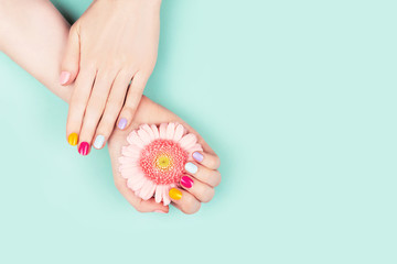 Woman hands with perfect manicure and flower.