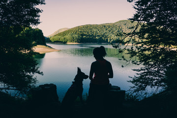 Silhouette of woman with dog sitting near lake