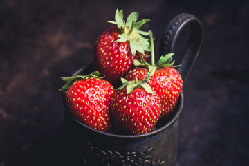 Ripe and juicy strawberries in old rustic metal cup. Selective focus. Shallow depth of field.  Fototapete