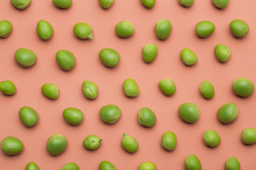 Set of peas placed orderly on salmon colored background Wall mural