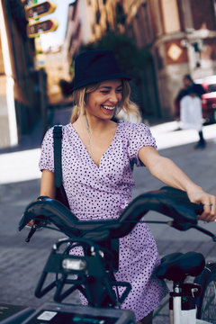 Attractive cheerful young woman taking a rental bike in city street