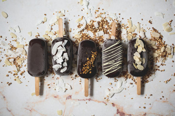 Top view of assorted chocolate ice cream popsicles covered with different toppings on a marble surface
