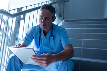 Male doctor using digital tablet on staircase in the hospital
