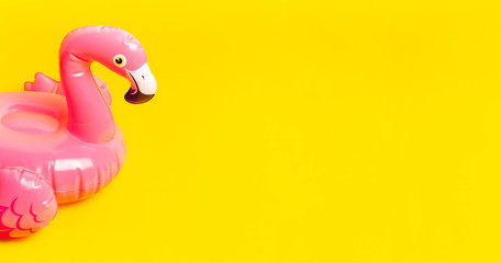 Creative summer beach concept. Inflatable pink mini flamingo on yellow background, pool float party. Flat lay, copy space. Flamingo Trend Inflatable Toy. Summer background. Layout for design