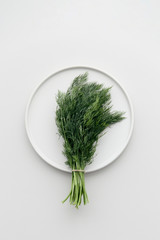A tied together bunch of fresh herbs dill on a white plate waiting to season a good fish dish.