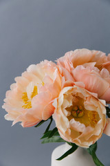 Close up of a bouquet of peach colored peonies in full bloom.