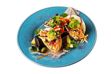 Closeup plate of mexican chicken tacos with vegetables and guacamole sauce served at baked paper isolated at white background.