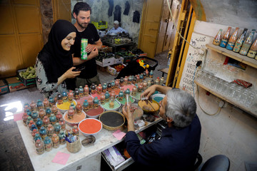 Palestinian craftsman Mohammed Al-Awawda speaks with customers as he creates coloured sand artworks at his souvenir shop in Hebron, in the Israeli-occupied West Bank