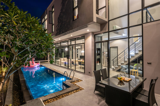 night exterior home with swimming pool in the house